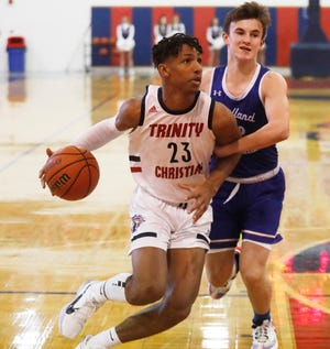 Trinity Christian's Marcus Ramon-Edwards (23) drives to the hoop in the first half of a nondistrict game Tuesday against Midland Christian at the Lions' Den. [Mark Rogers/For A-J Media]