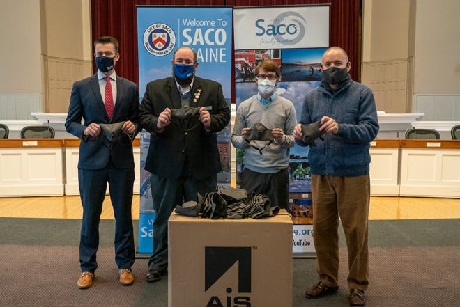 Officials in Saco, Maine display the face masks provided by AIS.