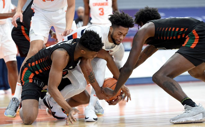 Miami guard Earl Timberlake, left, Syracuse forward Alan Griffin (0) and Miami center Nysier Brooks (3) scramble for a loose ball Tuesday at the Carrier Dome.