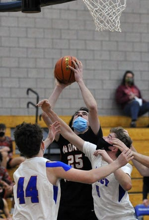 North Quincy's Daithi Quinn shoots over Quincy's Joseph Manton, left, and Coleman Rosa, right, during boys basketball action at Quincy High School, Tuesday, Jan. 19, 2021.