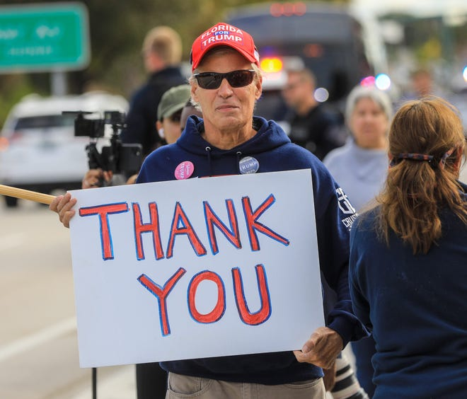 A man holds up a sign at Dreher Park in West Palm Beach thanking Donald Trump just before the 45th president takes his last motorcade ride from Palm Beach International Airport to Mar-a-Lago on Jan. 20.