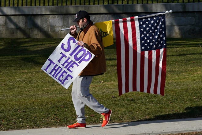 A protester walks in front of the Statehouse, Wednesday, Jan. 20, 2021, in Augusta, Maine. Law enforcement agencies stepped up patrols at the Statehouse to coincide with the inauguration of President Biden.