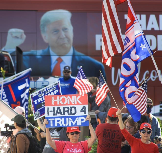 Crowds gather along Southern Boulevard near Dreher Park in West Palm Beach on Wednesday to say farewell to Donald Trump as he takes the final motorcade ride of his presidential term from Palm Beach International Airport to Mar-a-Lago.