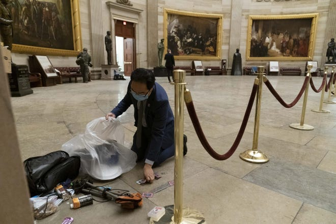 Rep. Andy Kim (D-N.J.), cleans up debris and personal belongings strewn across the floor of the Rotunda in the early morning hours of  Jan. 7, after protesters stormed the U.S. Capitol on Jan. 6.
