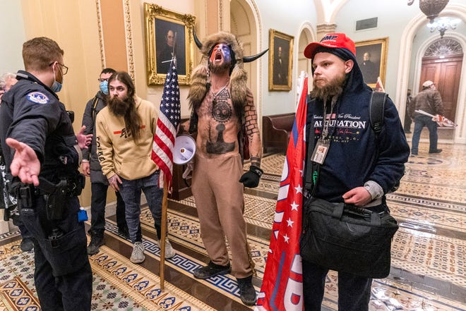 Supporters of President Donald Trump, including Jacob Chansley, center with fur hat, are confronted by police outside the Senate Chamber during the Jan. 6 riot in the U.S. Capitol.