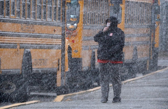 Jennifer Botelho, of Rumford, waits to pick up her daughter outside Myron J. Francis Elementary School in East Providence as snow falls Wednesday afternoon.