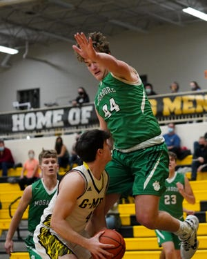 Mogadore sophomore Mason Williams jumps after Garfield junior Anthony Demma fakes a shot in Garrettsville on January 19.