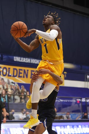 Kent State senior guard Michael Nuga gets wrapped up by Buffalo's Ronaldo Segu as he goes up for a slam dunk during the first half of Tuesday's game at the M.A.C. Center.