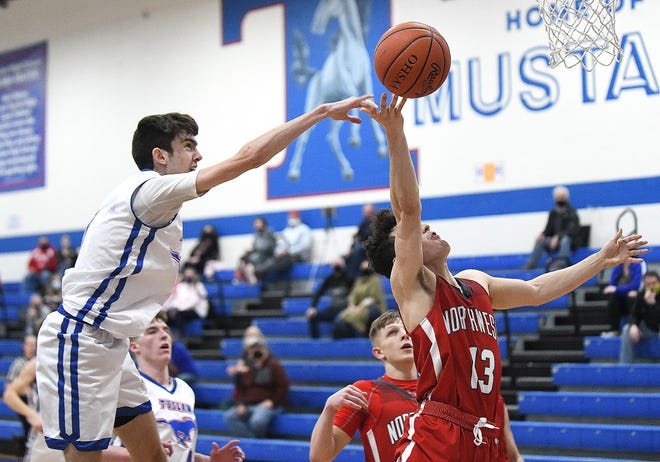 Ty Pratt of Tuslaw blocks the shot of Ethan Hyrne of Northwest in the second half at Tuslaw.