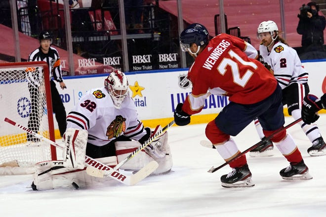 Chicago Blackhawks goaltender Kevin Lankinen (32), a former Rockford IceHogs player, stops a shot by Florida Panthers center Alexander Wennberg (21) during the second period Tuesday in Sunrise, Fla. Florida won in overtime as Lankinen stopped 23 shots in his NHL debut.