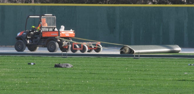 A construction worker uses a Kubota utility vehicle to help spread out the new artificial turf that is part of the $1.8 million renovation project for Dean Evans Stadium on Jan. 20.