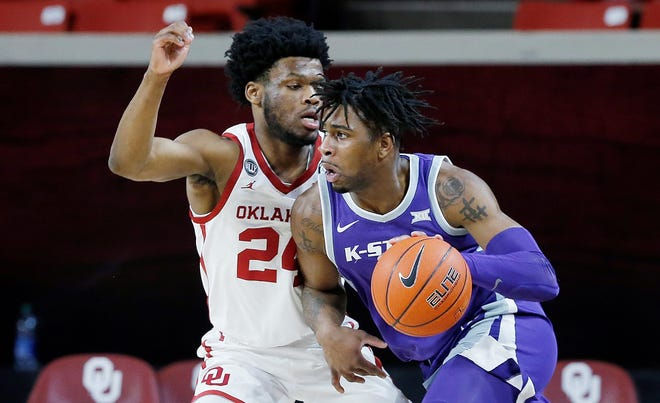 Kansas State forward Selton Miguel, right, drives against Oklahoma's Elijah Harkless during Tuesday's game in Norman, Okla.