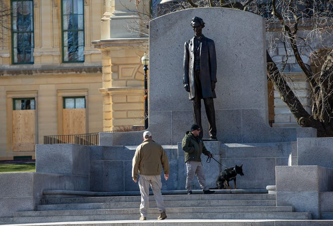 The Illinois State Police use a dog to check the area around the Abraham Lincoln statue at the Illinois State Capitol, Wednesday, January 20, 2021, in Springfield, Ill. Illinois Gov. JB Pritzker activated 250 members of the Illinois National Guard amid threats of armed protests in capital cities across the country during President-elect Joe Biden's inauguration. [Justin L. Fowler/The State Journal-Register]