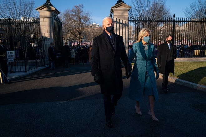President Joe Biden and first lady Jill Biden walk toward the North Portico of the White House.