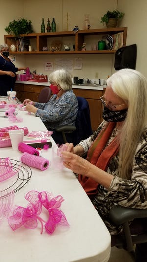 Iris Fairless, left, and Susie Hoskins work on crafting Valentine's Day wreaths at the Shawnee Senior Center Wednesday, Jan. 20. Vonda Bryce, seen in the background, led the activity.