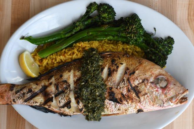 Το ολόκληρο snapper διαθέτει κίτρινο ρύζι, μπρόκολο και σάλτσα chimichurri στο Coquina Fishbar στο Wilmington, NC, Παρασκευή 15 Ιανουαρίου 2021. Το εστιατόριο άνοιξε μόλις στις 11 Ιανουαρίου, δίπλα στο Regal Mayfaire και διαθέτει μια ποικιλία από επιλογές θαλασσινών.      [MATT BORN/STARNEWS]