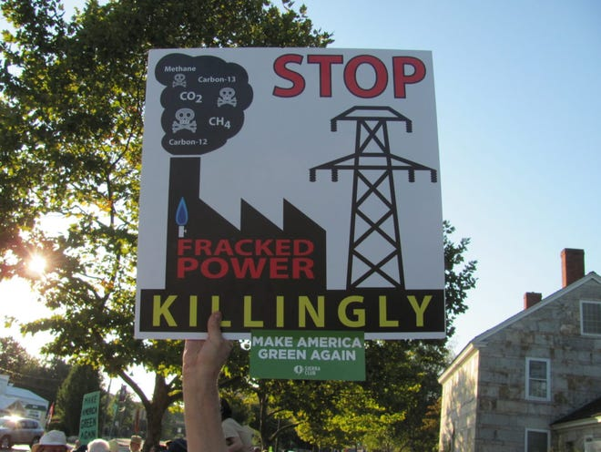 A protester holds up a sign calling for state officials to halt plans for the Killingly plant.