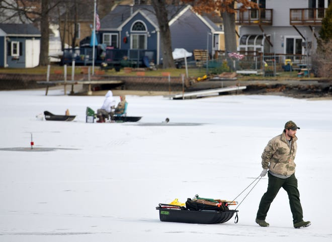 A local man tows a sled of fishing items from his spot on Indian lake Wednesday. In the background, two men from Cape Cod stake their fishing spot.