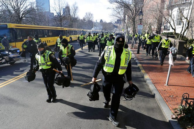 Boston police officers walk up Beacon Street toward the Massachusetts Statehouse on Sunday in anticipation of protests by right-wing groups.