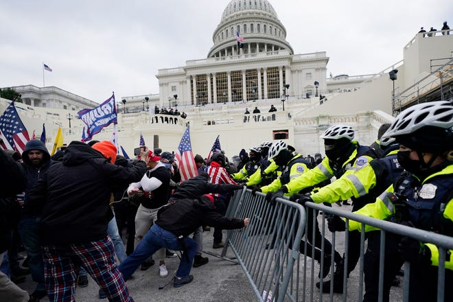 FILE - In this Wednesday, Jan. 6, 2021 file photo, Trump supporters try to break through a police barrier at the Capitol in Washington. In what could be the longest of legal longshots, several of those arrested for storming the U.S. Capitol are holding out hope that President Donald Trump will use some of his last hours in office to grant all the rioters a full and complete pardon. (AP Photo/Julio Cortez)