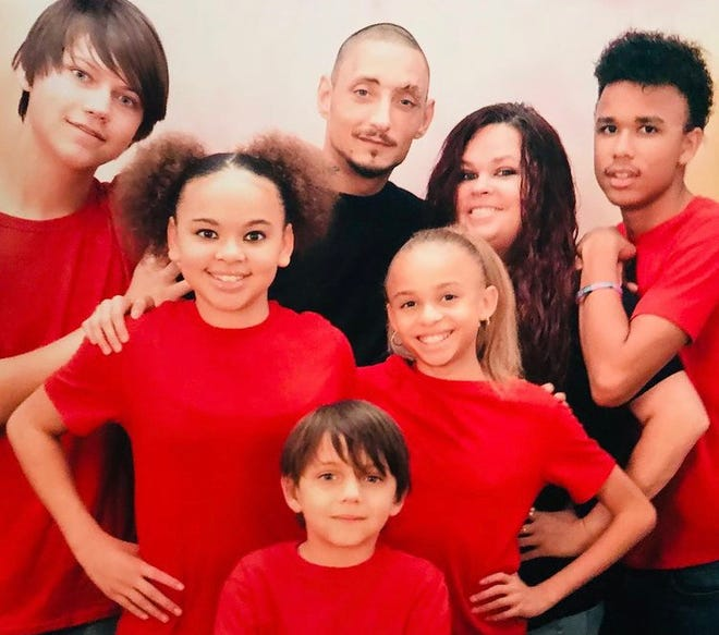 William Strickland and Heather Merritt, both in the back center, with her three children and his two children. Merritt says she helped Strickland Strickland when he was struggling with addiction. Merritt decided to end her own addiction to opioids after spending time in jail.
