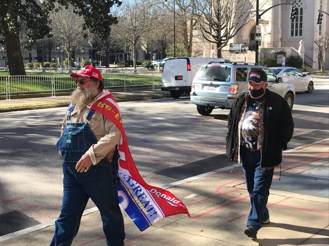 A pair of protestors walk outside the N.C. State Capitol Building in Raleigh on Jan. 20, 2021.
