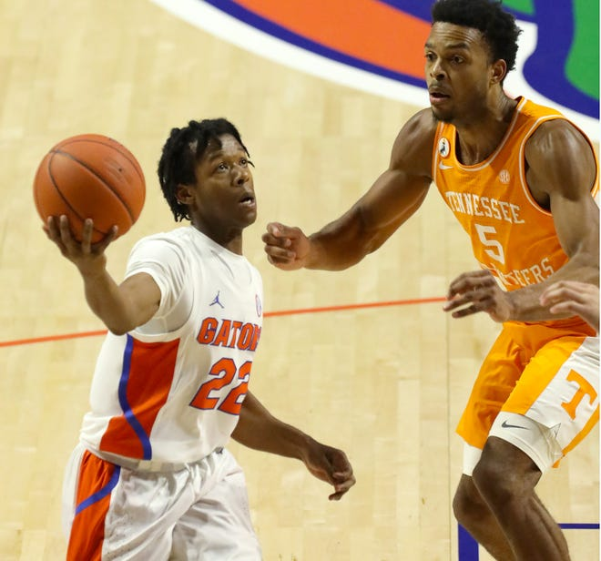 Florida guard Tyree Appleby takes the ball to the basket for a score past Tennessee guard Josiah-Jordan James during Tuesday's game at Exactech Arena.