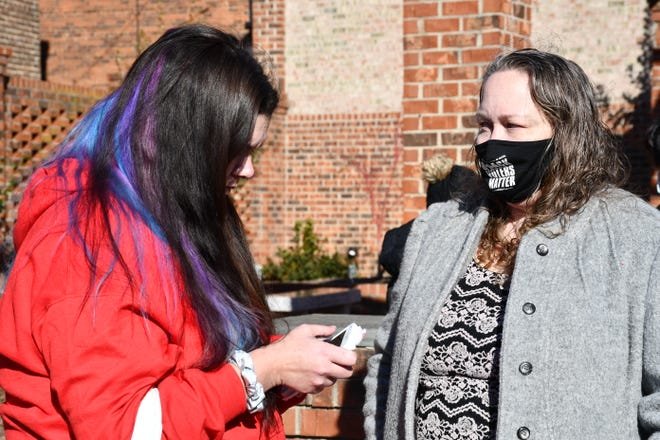 Amy Cooper speaks with attorney Jamie Paulen at a tenants' rights demonstration on Wednesday in Graham.