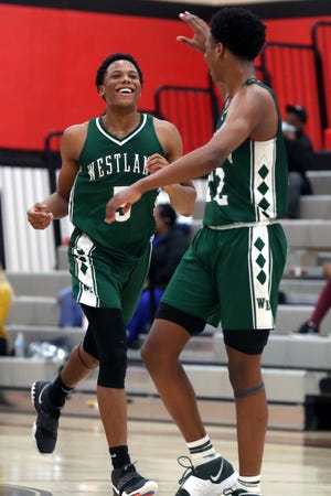 Westland's Derrick Bogay (facing) celebrates with Sohn McGee after scoring off a turnover during a 52-51 win at Groveport on Jan. 19. Bogay recently returned to the Cougars after sitting out because of COVID-19 concerns.