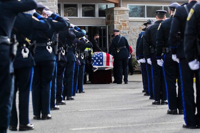 The casket carrying Norton Police Det. Sgt. Stephen Desfosses, who passed away from COVID-19 on Jan. 13, 2021, is led into St. Mary's Catholic Church in Norton on Tuesday, Jan. 19, 2021.