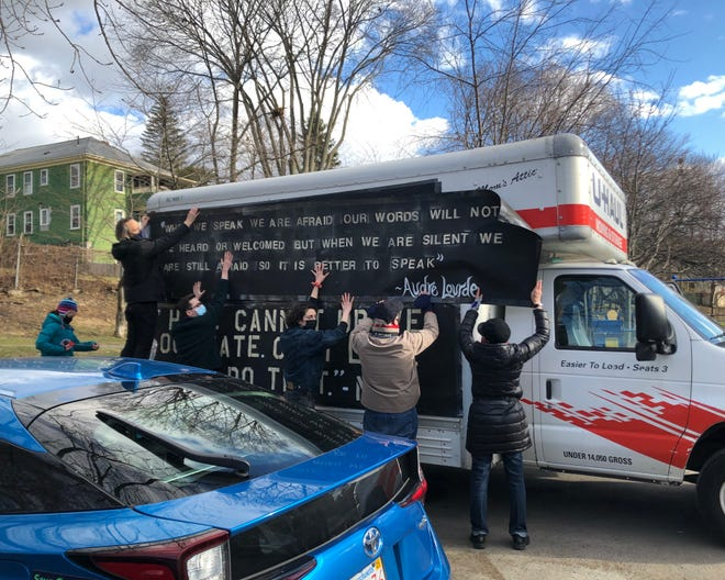 Multiple community members help to tape a banner to the side of one of the two Uhaul trucks that led the parade in Watertown on Jan. 18, 2021.