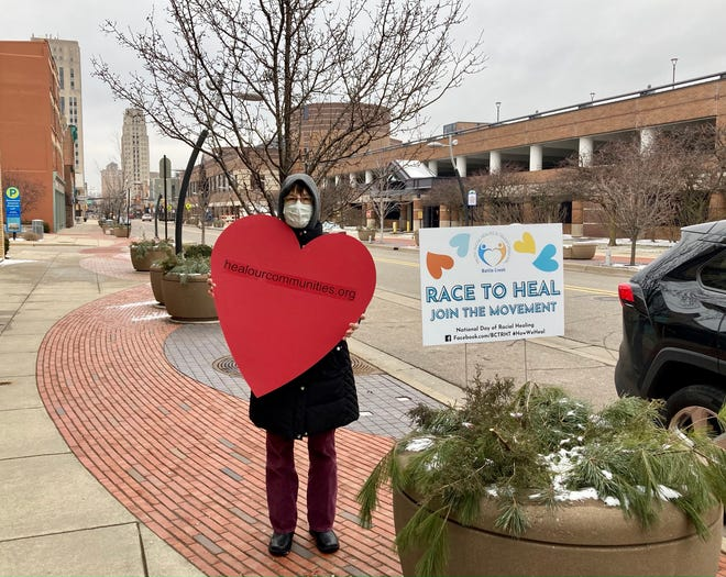 Kathy Antaya, a member of the Battle Creek Coalition for Truth, Racial Healing and Transformation, distributes hearts and signs in downtown Battle Creek on Jan. 19, 2021.