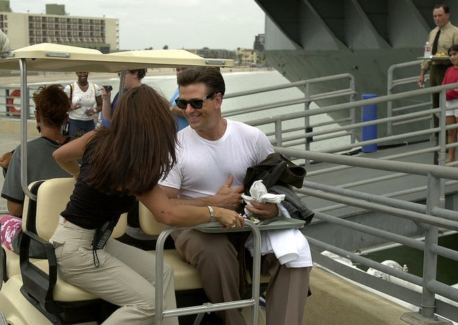 "Alec Baldwin heads down the pier at the USS Lexington Museum on the Bay in Corpus Christi towards the trailers for lunch break during the shooting of the movie ""Pearl Harbor"" on July 31, 2000."