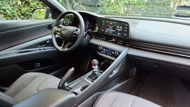 """The sporty interior of the 2021 Hyundai Elantra N Line includes standard manual transmission and an """"oh, crap!"""" handle for the passenger when the g-loads get intense."""