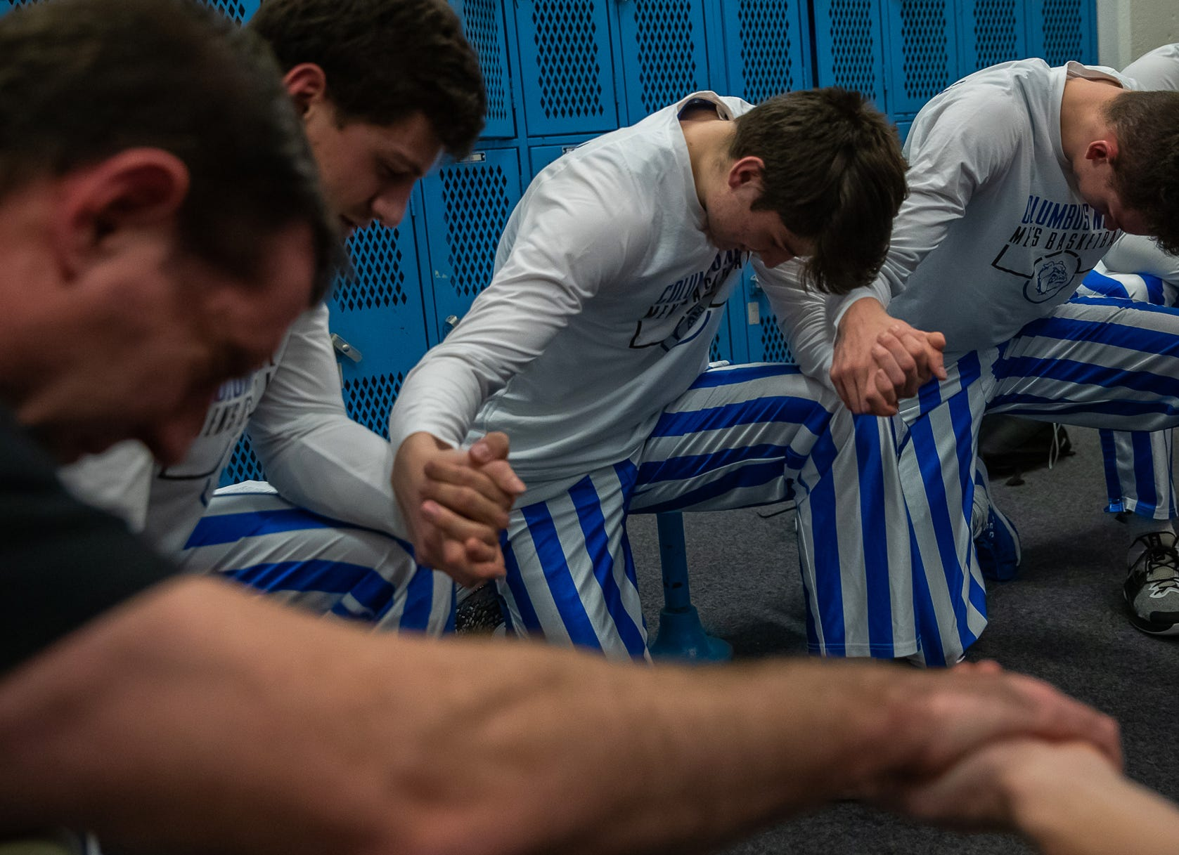 Columbus North head basketball coach Paul Ferguson kneels with his players during a prayer before their home, senior night basketball game against the Seymour Owls at Columbus North High School's Memorial Gymnasium on Tuesday, Feb. 25, 2020.