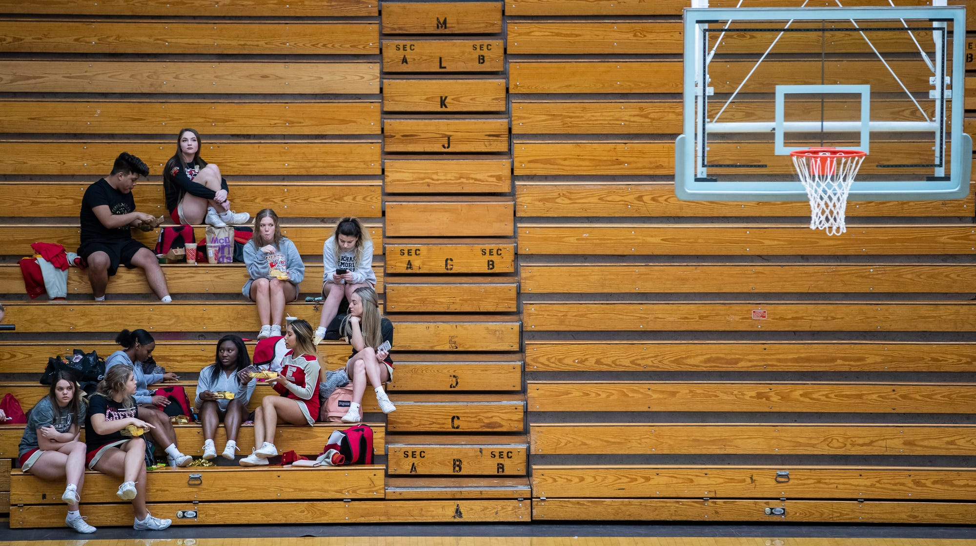 The Elkhart Memorial Chargers' cheerleaders grab a quick snack before the Chargers' boys sectional basketball game against Northridge inside the Elkhart North Side Gymnasium on Friday, March 6, 2020.