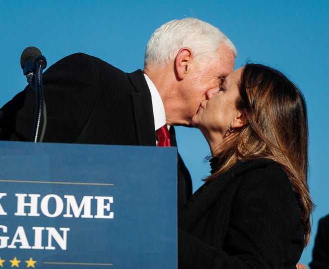 Former Vice President Mike Pence kisses his wife, Karen Pence, as he gives a speech to a small crowd on Wednesday, Jan. 20, 2021 at Columbus Municipal Airport in Columbus, Ind.