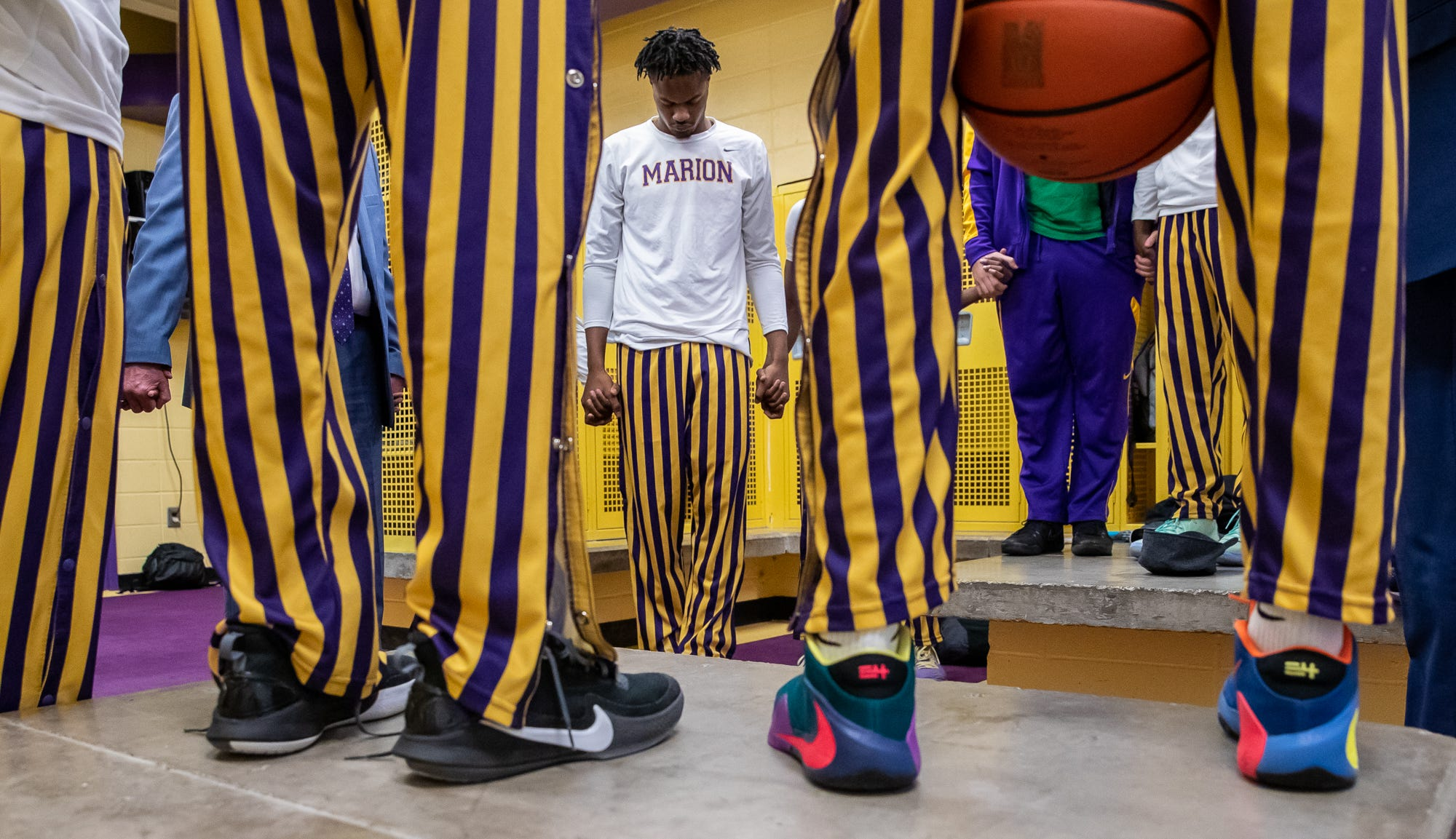 Marion Giants' Brendon Martin says a prayer alongside his teammates and coach inside Marion High School's Bill Green Arena before the teams varsity basketball game against the Fort Wayne Snyder Panthers on Friday, Feb. 28, 2020.