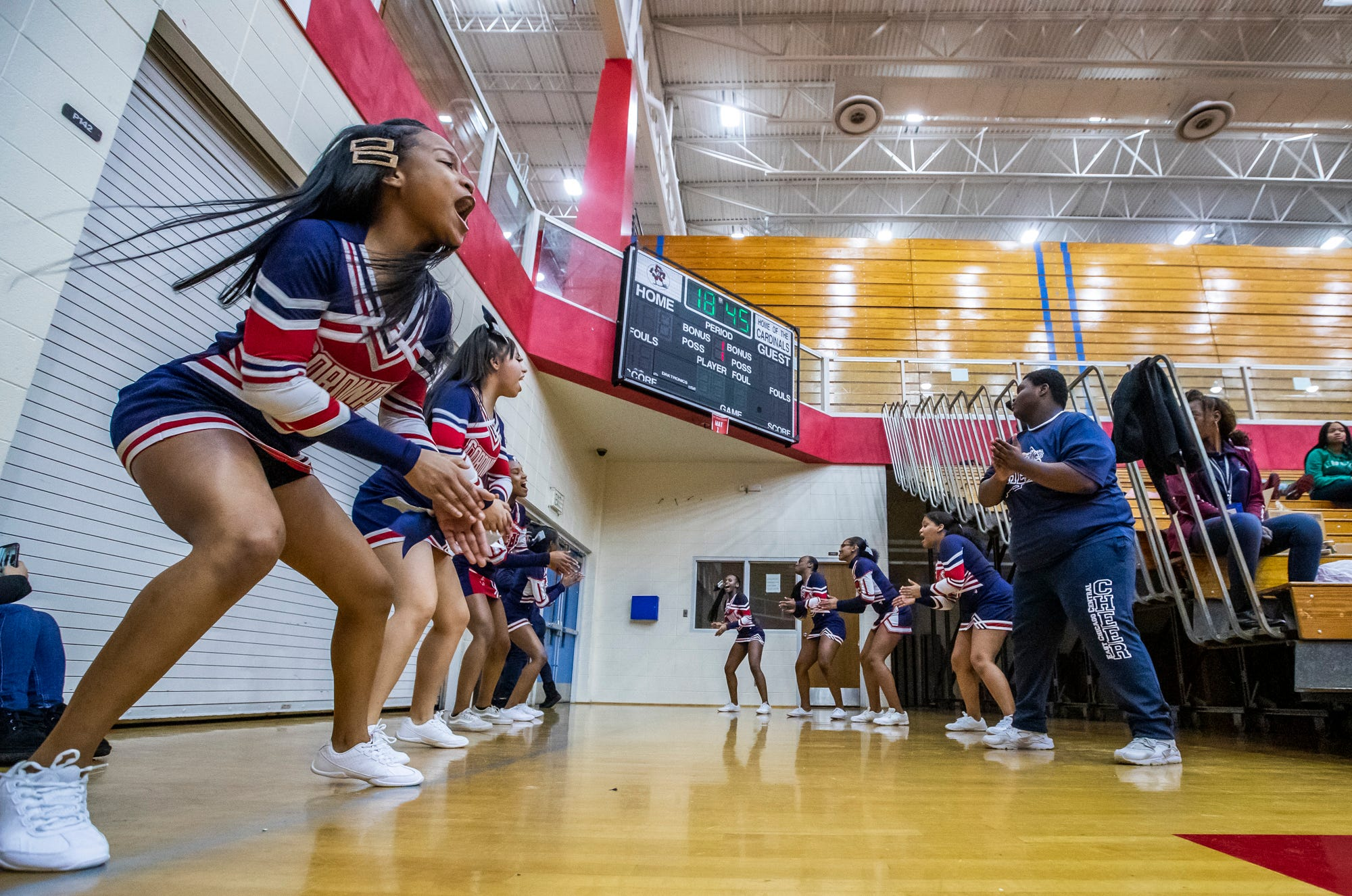Ashanti Bell (left) and the rest of the East Chicago cheerleaders welcome the varsity boys team to the court for the game against Hammond at East Chicago Central High School's John A. Baratto Athletic Center on Tuesday, Jan. 21, 2020.