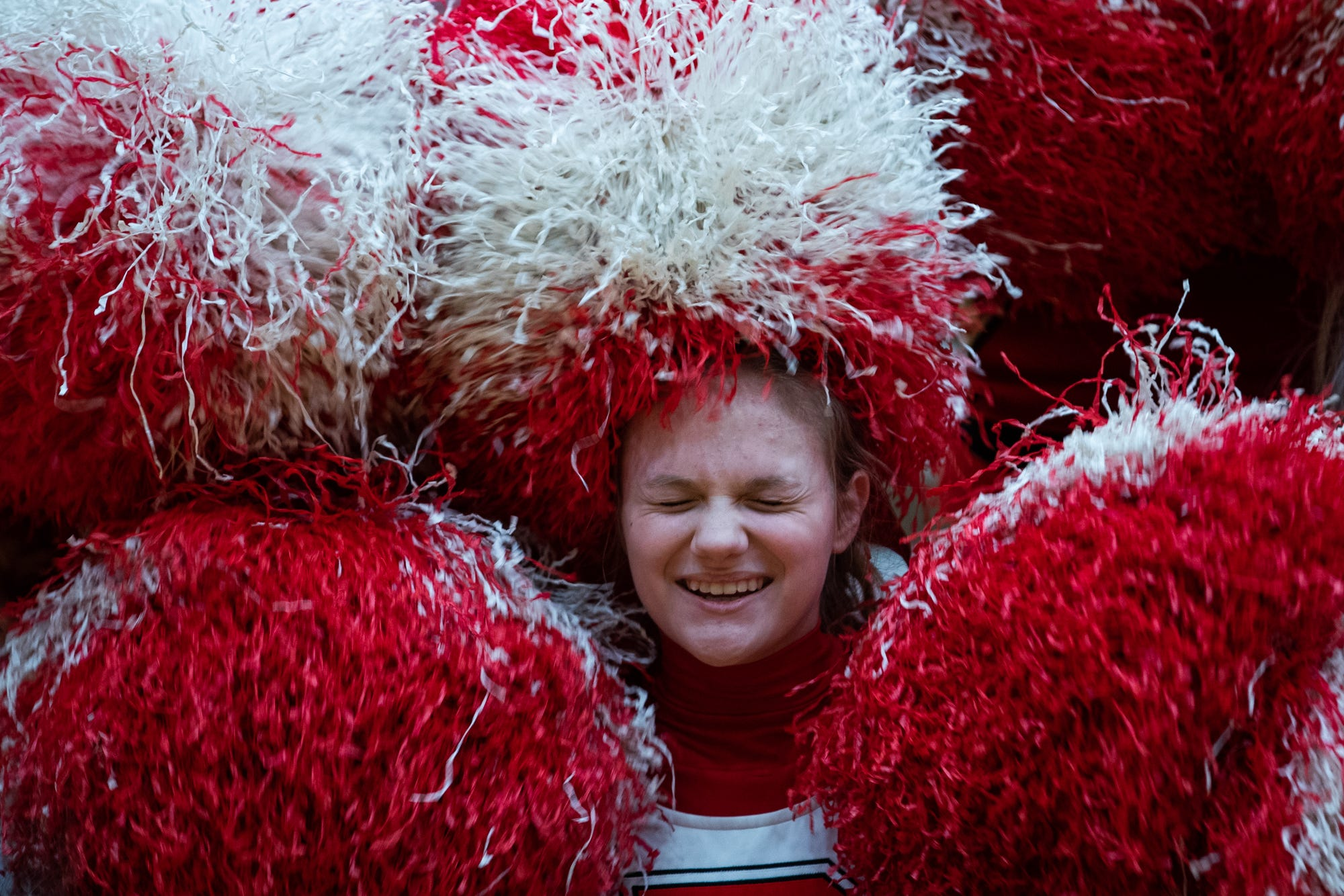 Taylor Mikesell, a freshman cheerleader at Richmond High School, giggles while making pompom letters with the rest of the cheer team before the varsity boys basketball game against the Kokomo Wildkats inside the Tiernan Center gymnasium in Richmond, Ind., on Friday, Feb. 14, 2020.