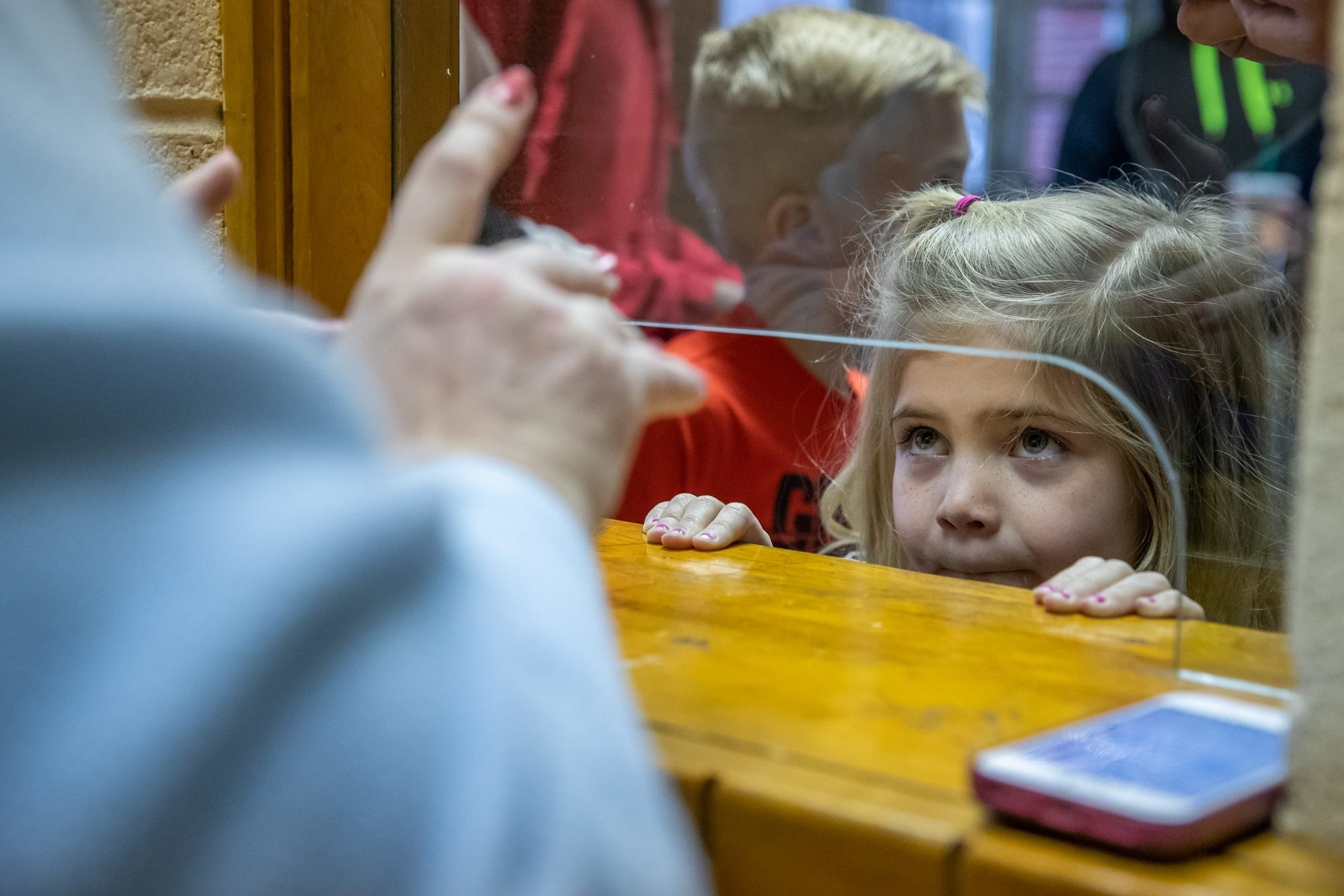 Serena Kesler, 6, of Warsaw, Ind., waits for her family's tickets before the start of a boys sectional tournament from the Elkhart North Side Gymnasium on Friday, March 6, 2020.