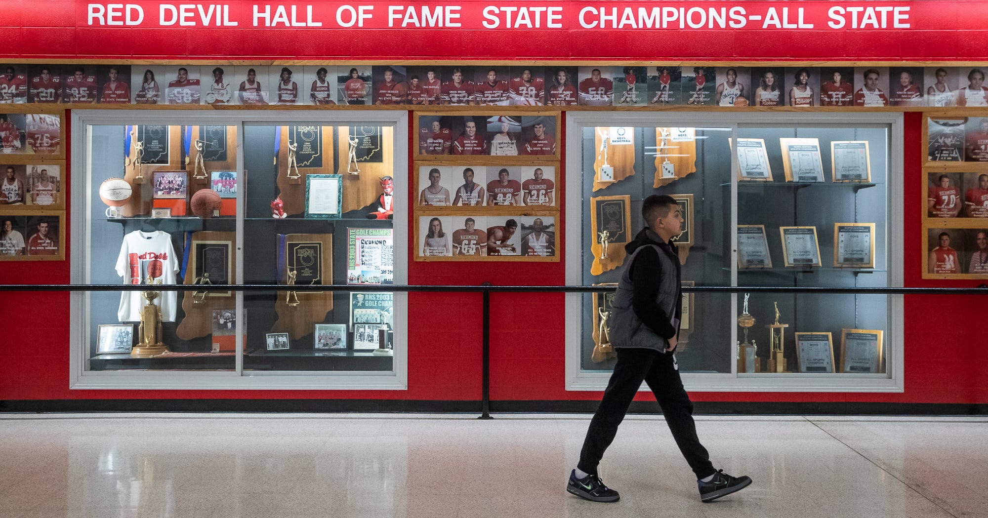 In front of the Red Devil Hall of Fame wall, Taysen Stewart, 11, of Richmond, Ind., follows closely behind his parents as they make their way to their seats for the Richmond Red Devils' home boys varsity game against the Kokomo Wildkats in Richmond, Ind., on Friday, Feb. 14, 2020.