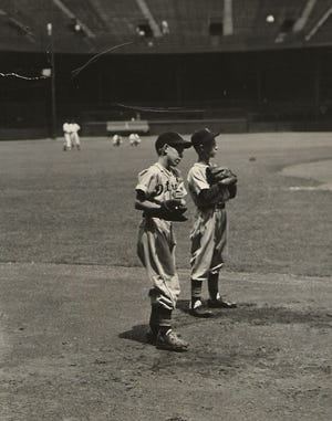 Elliott Trumbull (left) and Mickey Briggs prepare to catch balls at Briggs Stadium during batting practice proudly wearing their Tiger uniforms.