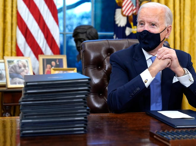 President Joe Biden waits to sign his first executive order in the Oval Office of the White House on Jan. 20, 2021, in Washington. Behind him is a bust of Arizona native and civil rights leader Cesar Chavez.