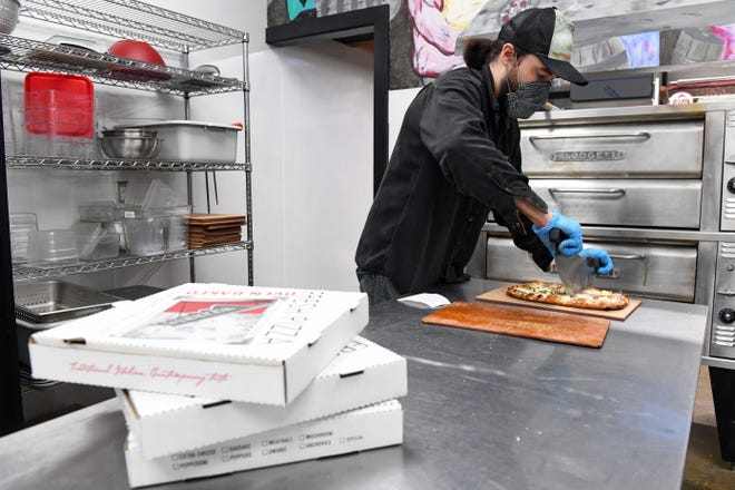 Johnny Friedow boxes pizzas on Tuesday, January 19, in the kitchen at Monk's Ale House in Sioux Falls.