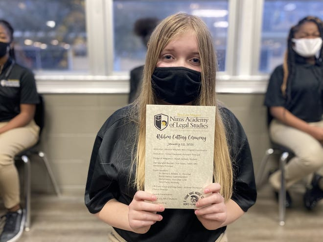 A Nims Middle School student holds a program to celebrate the ribbon cutting on an R. Frank Nims Middle School pre-law magnet program, Jan. 2021.