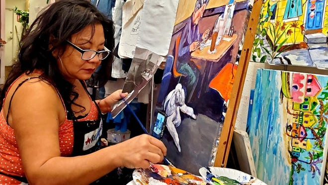 Maria Paz, a Lake Worth artist, paints a portrait of the late Larry Cusick, of Stuart, who was a regular diner at Alice's Family Restaurant. The portrait will be hung above the booth Cusick always sat in to honor and remember him.