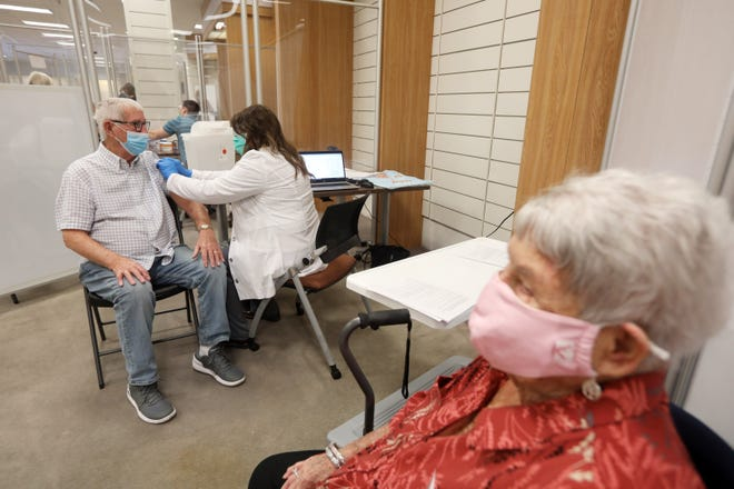 JoAnn Grubb waits while her husband Jim gets his COVID-19 vaccination at Genesis HealthCare's COVID-19 vaccination clinic in the former Elder-Beerman store located in the Colony Square Mall on Wednesday.