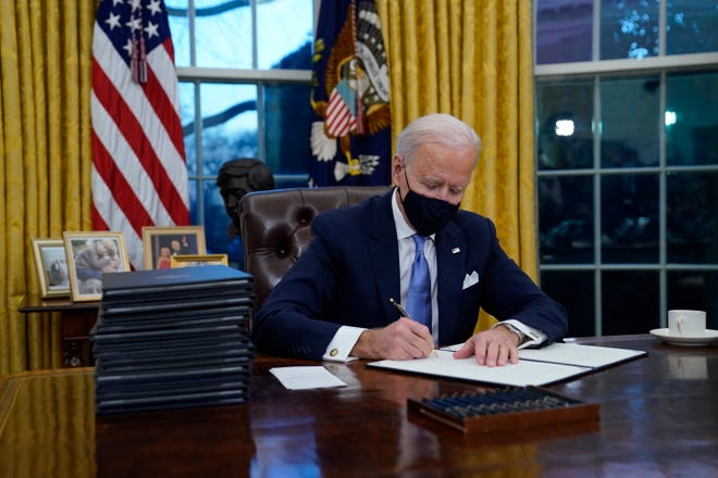 President Joe Biden signs his first executive orders in the Oval Office of the White House on Wednesday, Jan. 20, 2021, in Washington.