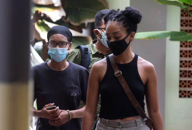 American graphic designer Kristen Antoinette Gray, left, walks with her partner Saundra Michelle Alexander, right, to be tested for the coronavirus at a hospital in Denpasar, Bali, Indonesia on  Jan. 20, 2021. Gray, who arrived in Bali in January 2020 and wound up staying through the coronavirus pandemic, is being deported from the Indonesian resort island over her viral tweets that celebrated it as a low-cost, queer-friendly place for foreigners to live.